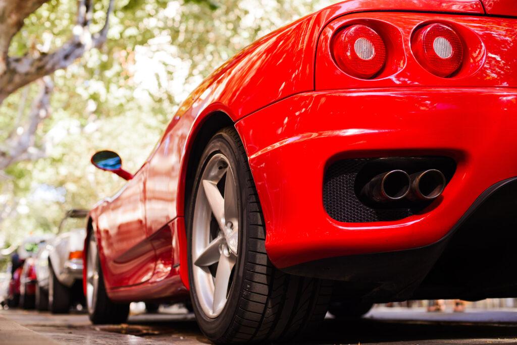 Super auta - na zdjęciu tył Ferrari sportowego, pod jakimś niewyraźnym drzewem.