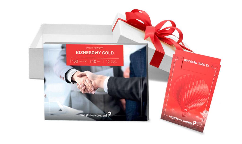 Prezenty biznesowe, na zdjęciu pakiet biznesowy gold, gift card oraz białe pudełko z kokardą.