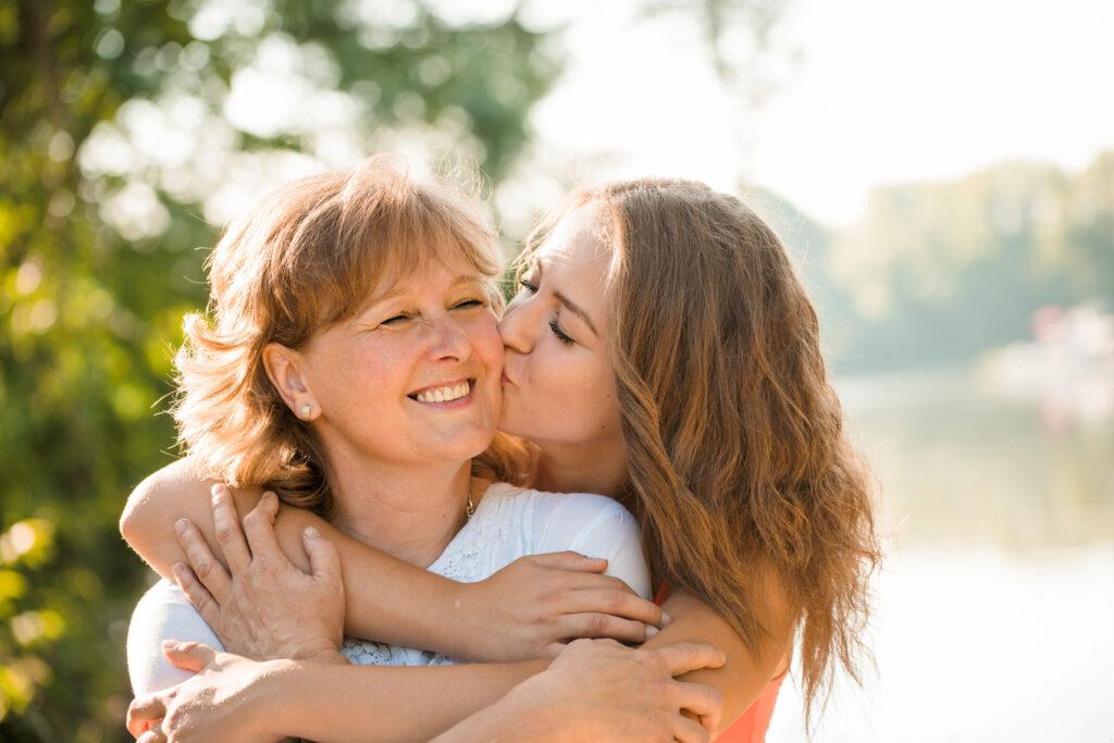Dzień Mamy - Córka obejmuje i całuje mamę, która jest uśmiechnięta, w policzek, w tle rozmazane drzewo.