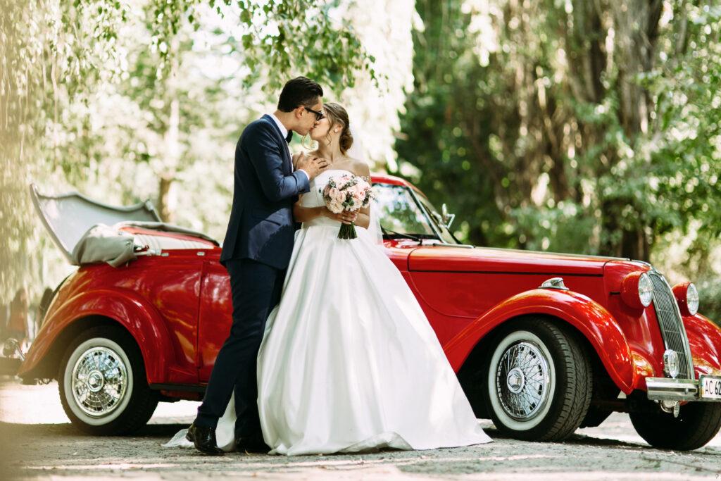 Prezenty ślubne - para młoda całuje się, w tle stary, czerwony samochód.