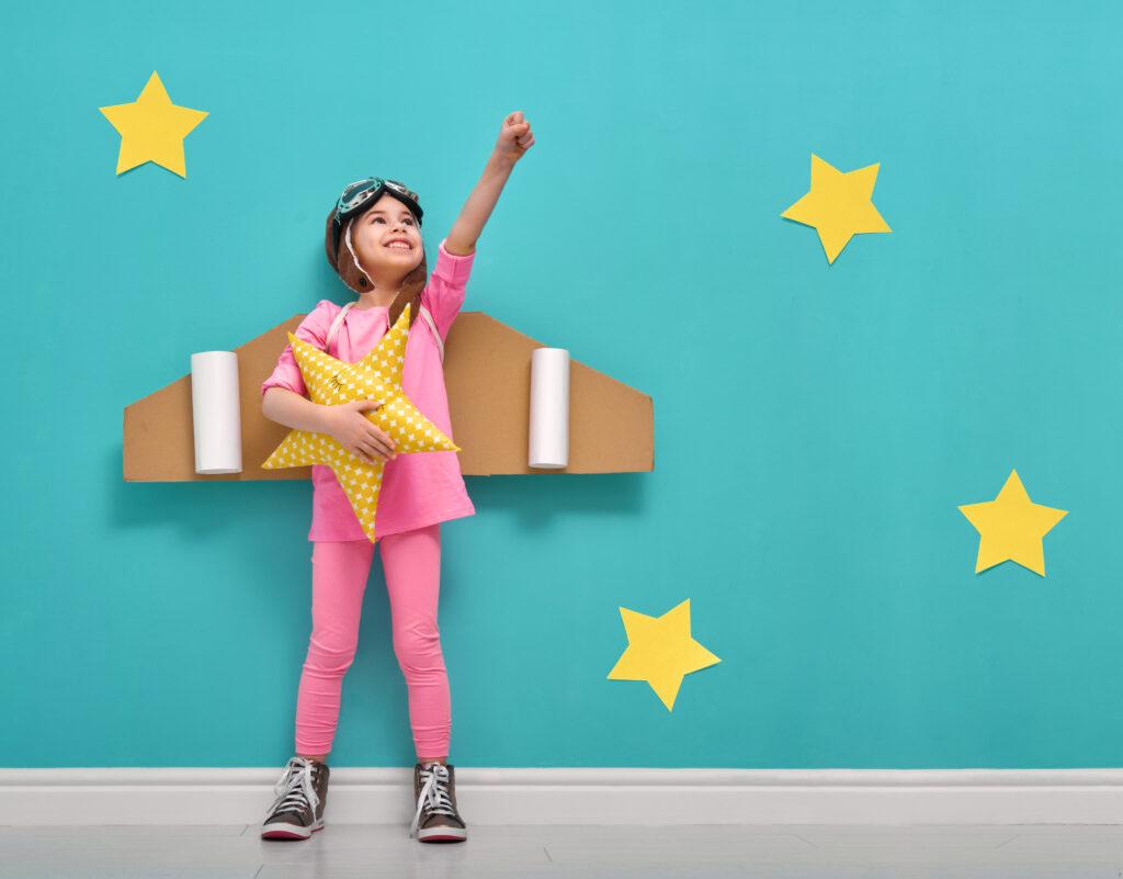 Dzień Dziecka - mała dziewczynka, ze skrzydłami zrobionymi z kartonu, trzyma w ręku gwiazdkę pluszową i wyciąga rękę ku niebu. Per asper ad astra.