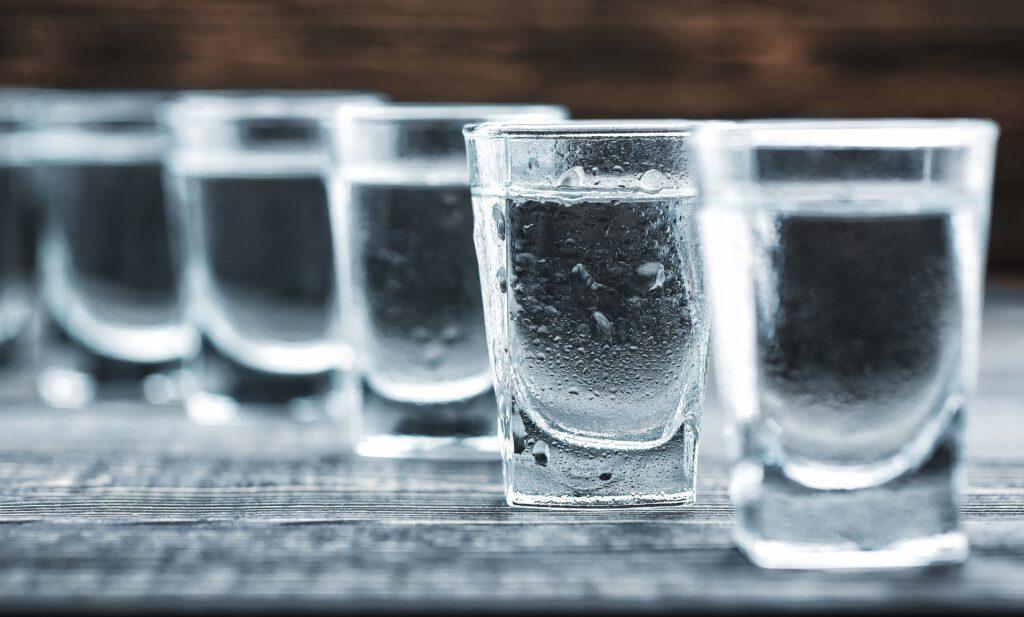 Rząd kieliszków wódki. Wódka ewidentnie zimna, czysta.