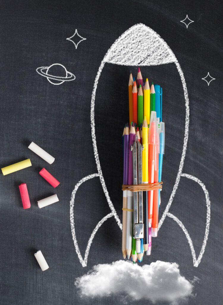 Prezent na zakończenie roku szkolnego dla dziecka - Kosmiczna rakieta, narysowana kredą na tablicy, złożona z kredek - ewidentnie startuje.