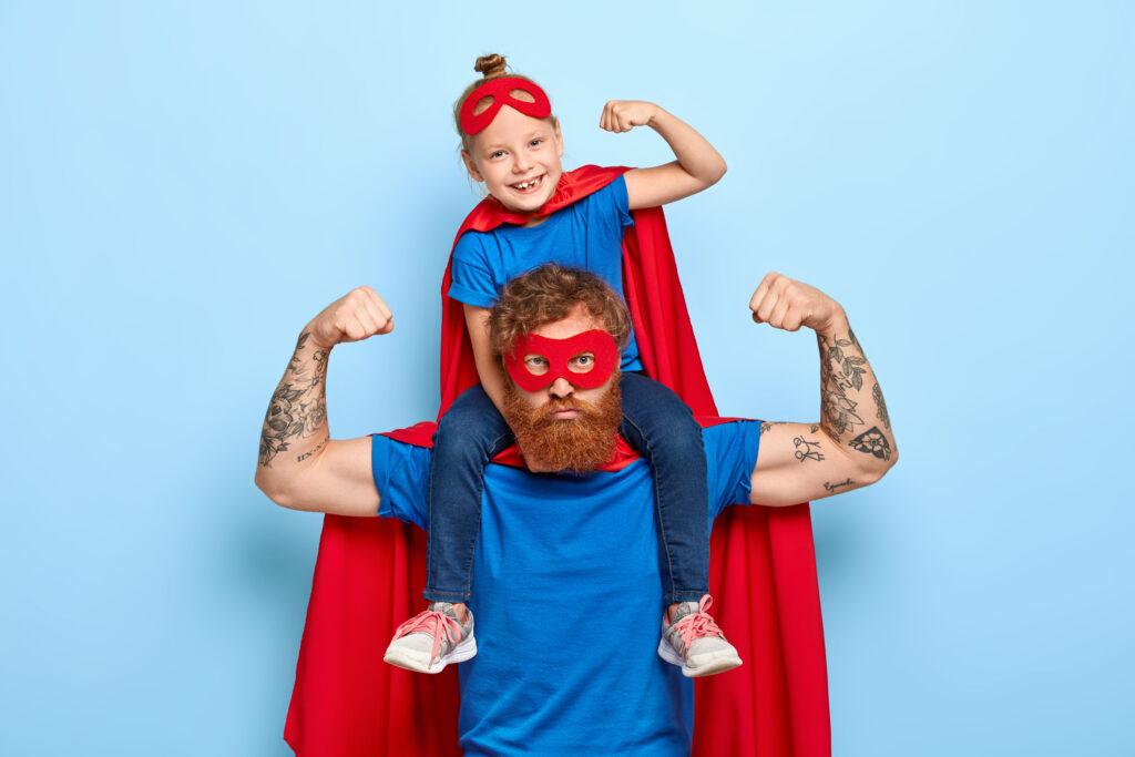 """Dzień Ojca - Mężczyzna w przebraniu superbohatera trzyma """"na barana"""" swoja córkę, która tez jest w przebraniu superbohatera! Ojciec pokazuje również, że """"jest moc"""", dumnie prężąc muskuły. Obydwoje sprawiają wrażenie szczęśliwych."""
