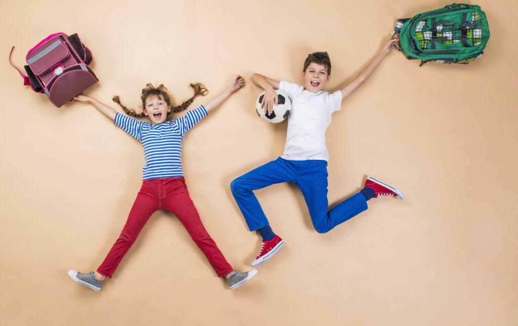 Dwójka dzieci - chłopiec i dziewczynka, leżą na podłodze i trzymają tornistry. Są szczęśliwi, że wracają do szkoły