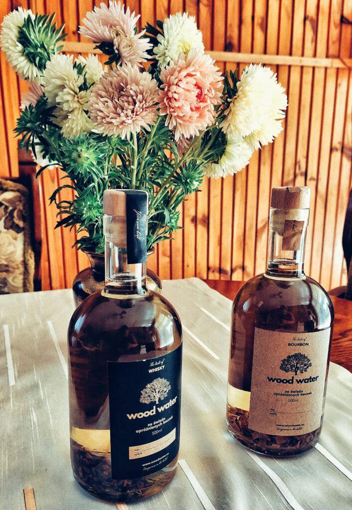 Dwie butelki stoją na stole - whisky i bourbon z zestawu Stwórz Własny Alkohol