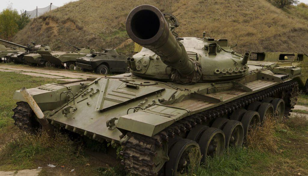Na zdjęciu czołg z ogromną lufą, skierowaną w stronę oglądającego to zdjęcie. W tle inne czołgi i jakiś pagórek.