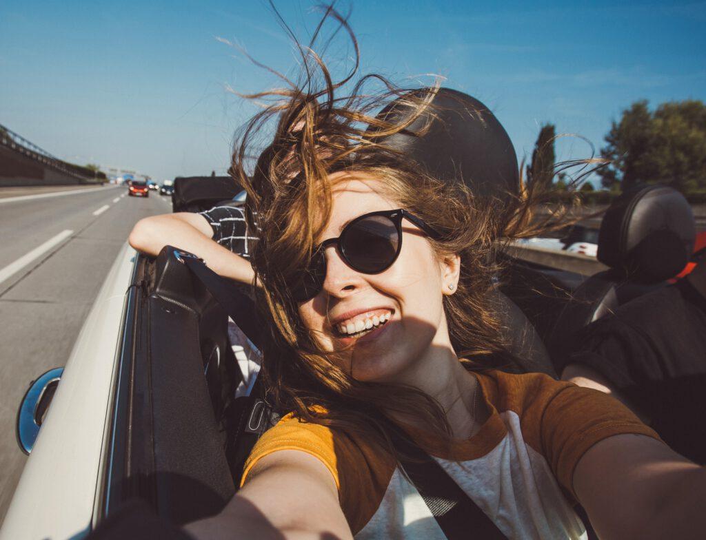 Uśmiechnięta kobieta, jadąca samochodem jako pasażer, robi selfie. Wiatr rozwiewa jej włosy.