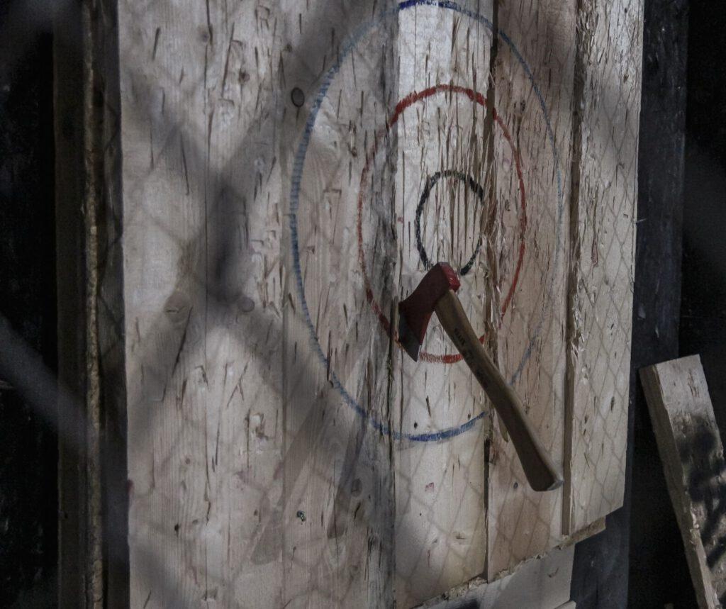 Rzucanie Siekierami do Celu, czyli Axe Throwing. Przygoda polega na rzucaniu siekierami do tarczy i zbieraniu punktów.