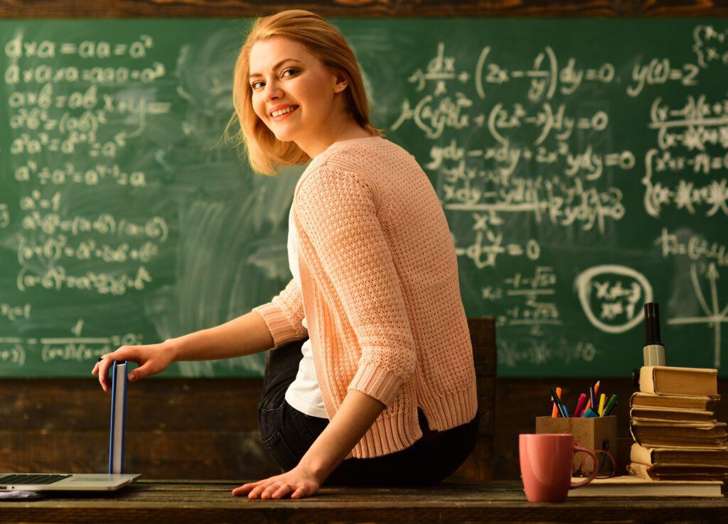 Dzień Nauczyciela - nauczycielka, w tle zapisana tablica, laptop, kubek kawy, dziennik. Prezent z okazji Dnia Nauczyciela