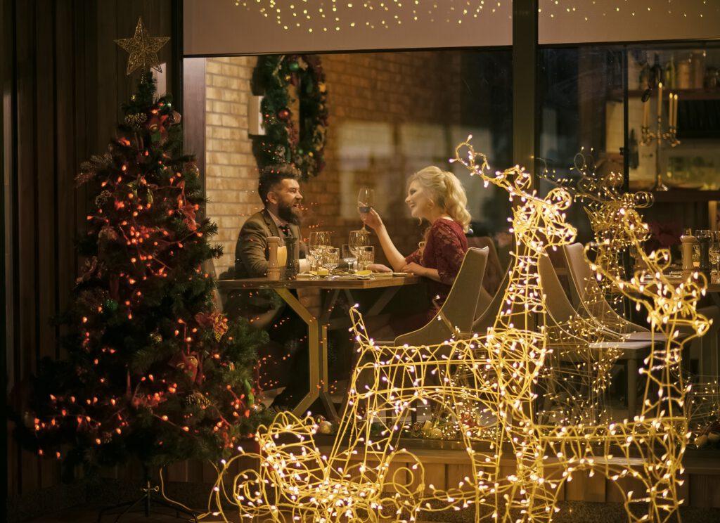Para je kolację, obok przystrojona choinka i ozdoby świąteczne. Domowe zacisze i oryginalne prezenty na święta.