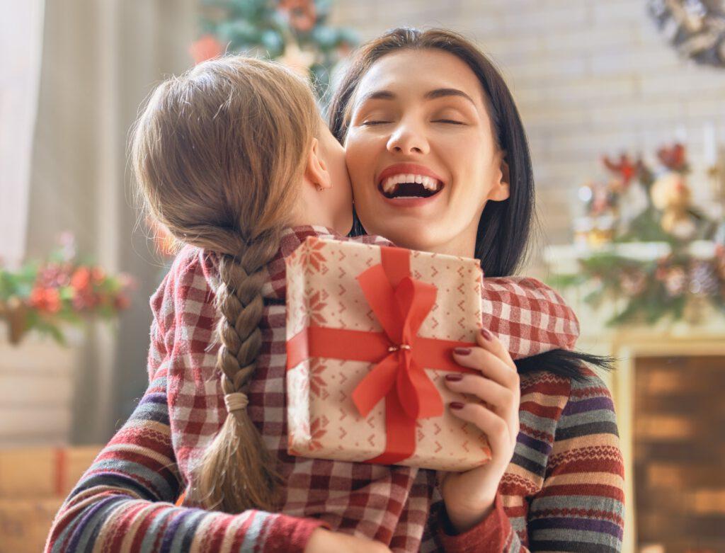 Prezent dla mamy - na zdjęciu mama otrzymuje prezent na święta i jest szczęśliwa.