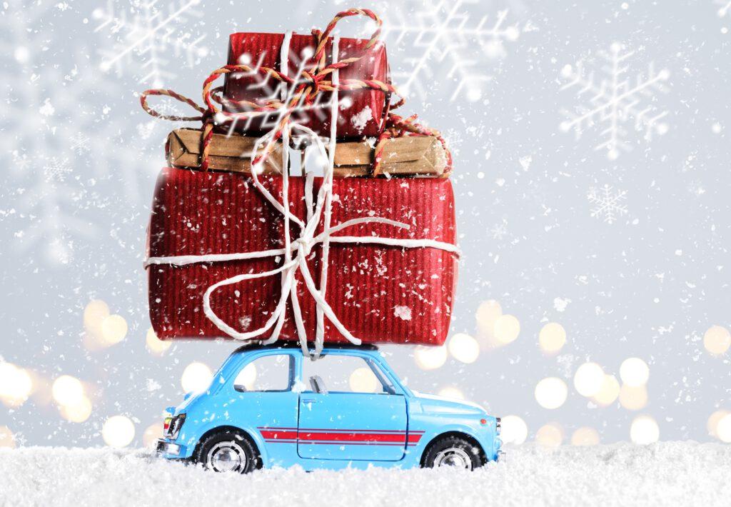 Mały samochód wiezie na dachu prezenty na święta. Świetne prezenty nie muszą być wielkie!