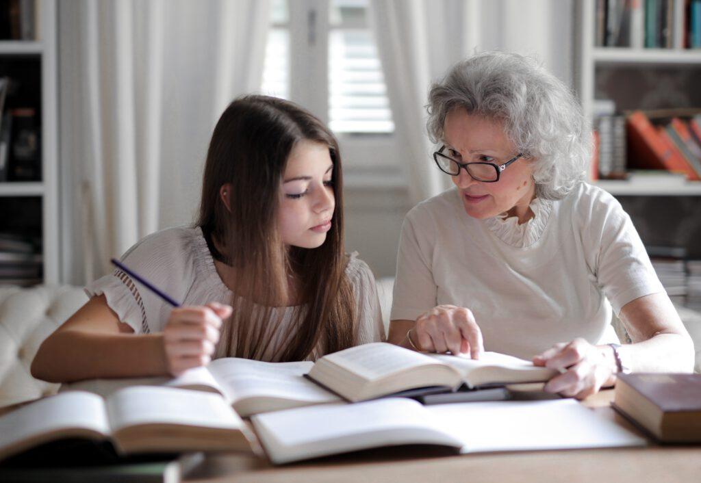 Dzień Babci- Babcia odrabia z wnuczką lekcje.