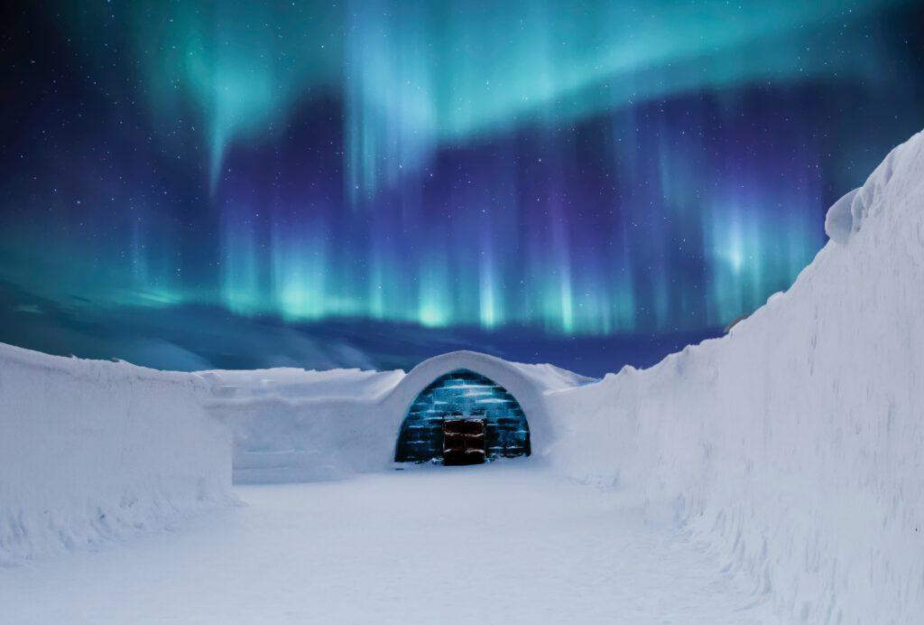 Iglo w śniegu i widok na zorze polarną.