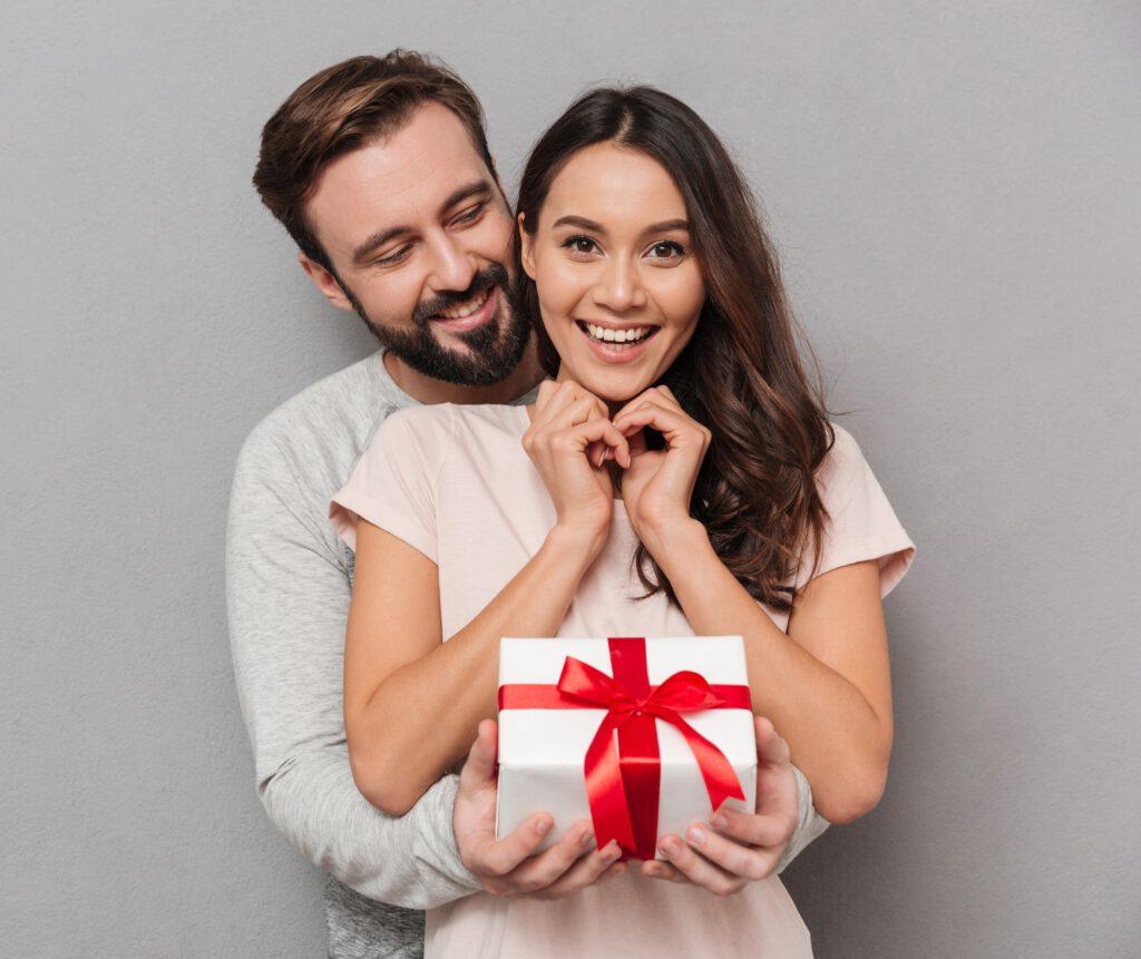 Para, mężczyzna wręcza kobiecie prezent na rocznicę ślubu
