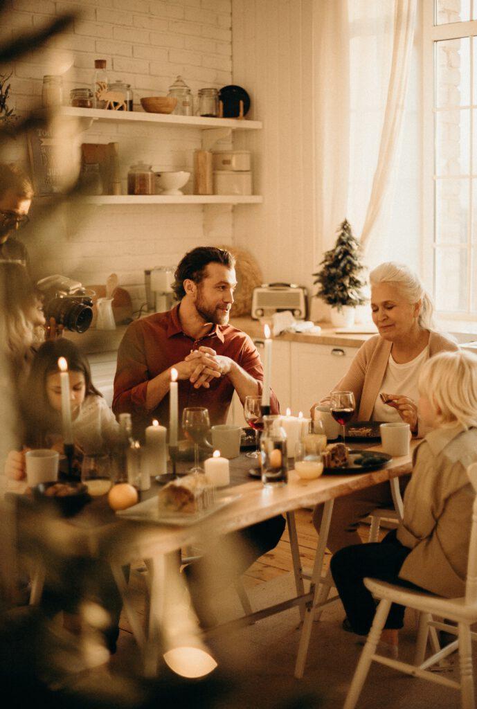 Przy zastawionym i rozświetlonym świecami stole kuchennym siedzi rodzina z dziećmi podczas posiłku,