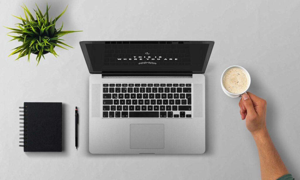Widok miejsca do pracy z komputerem. Laptop kubek kawy notes z długopisem.
