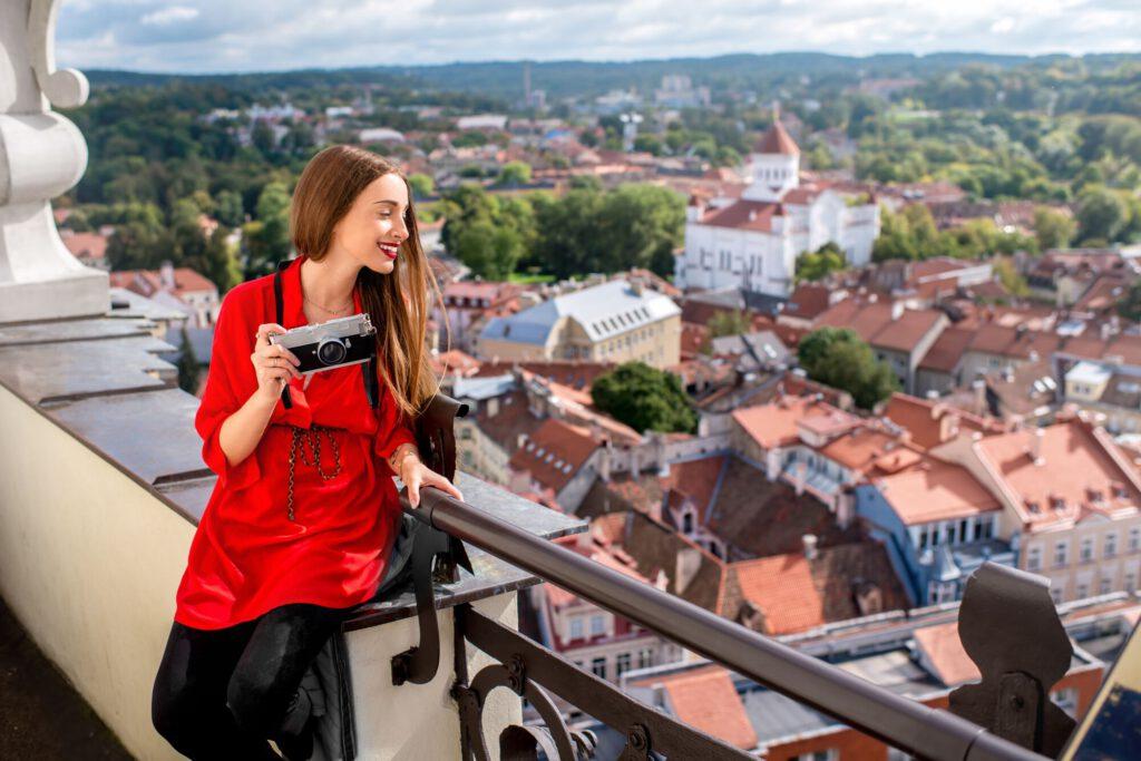 Uśmiechnięta pani na dachu budynku, trzyma w ręce aparat fotograficzny i podziwia miasto