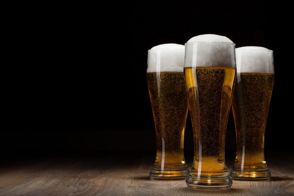 3 kufle świeżo nalanego piwa, stojące na ciemnych deskach, jedno bliżej, dwa dalej. Tło czarne. Symbol na dzień św. Patryka.