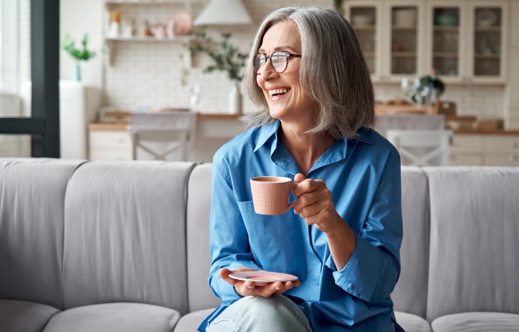 Uśmiechnięta kobieta w wieku 50 lat siedzi na kanapie w domu, trzyma  filiżankę z kawą.