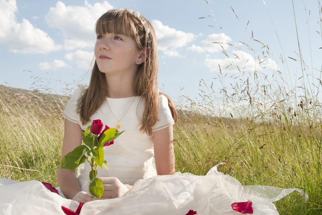 Dziewczynka w białej sukni siedzi na łące i trzyma czerwoną różę.