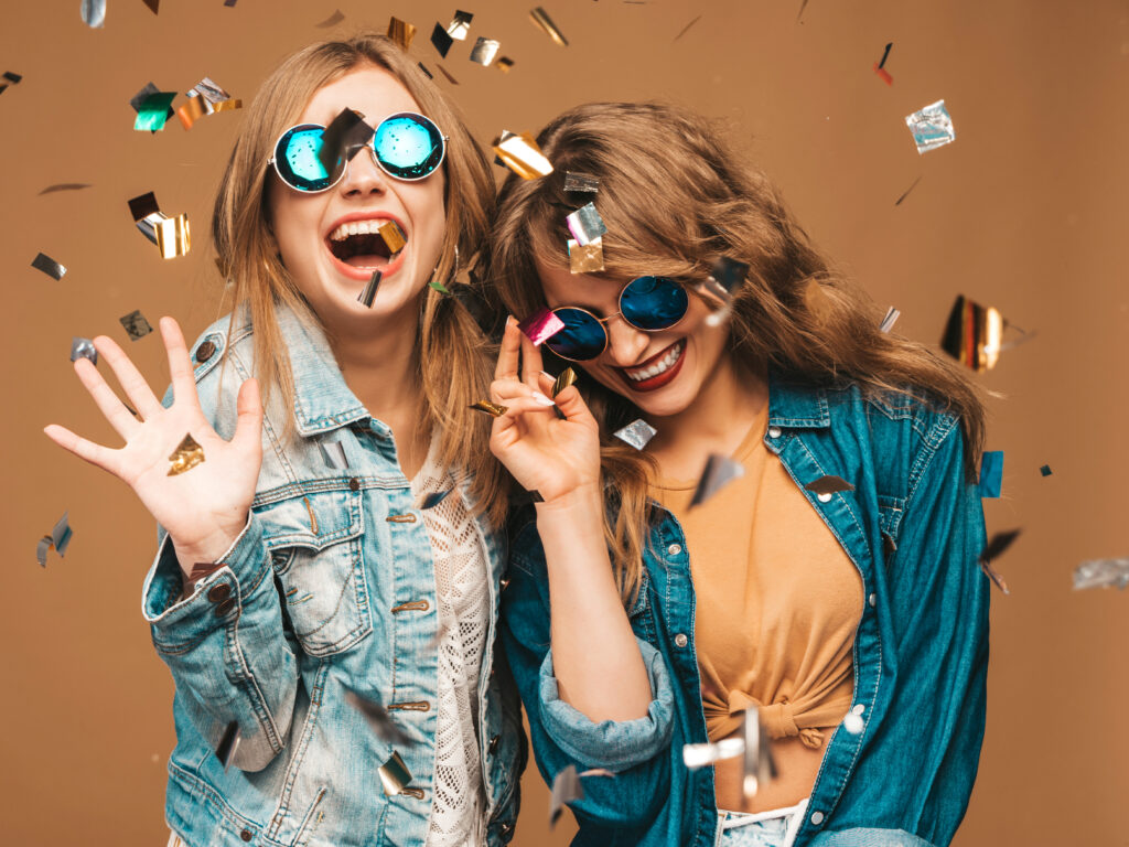 2 młode, uśmiechnięte przyjaciółki w okularach przeciwsłonecznych. Sypię się konfetti.