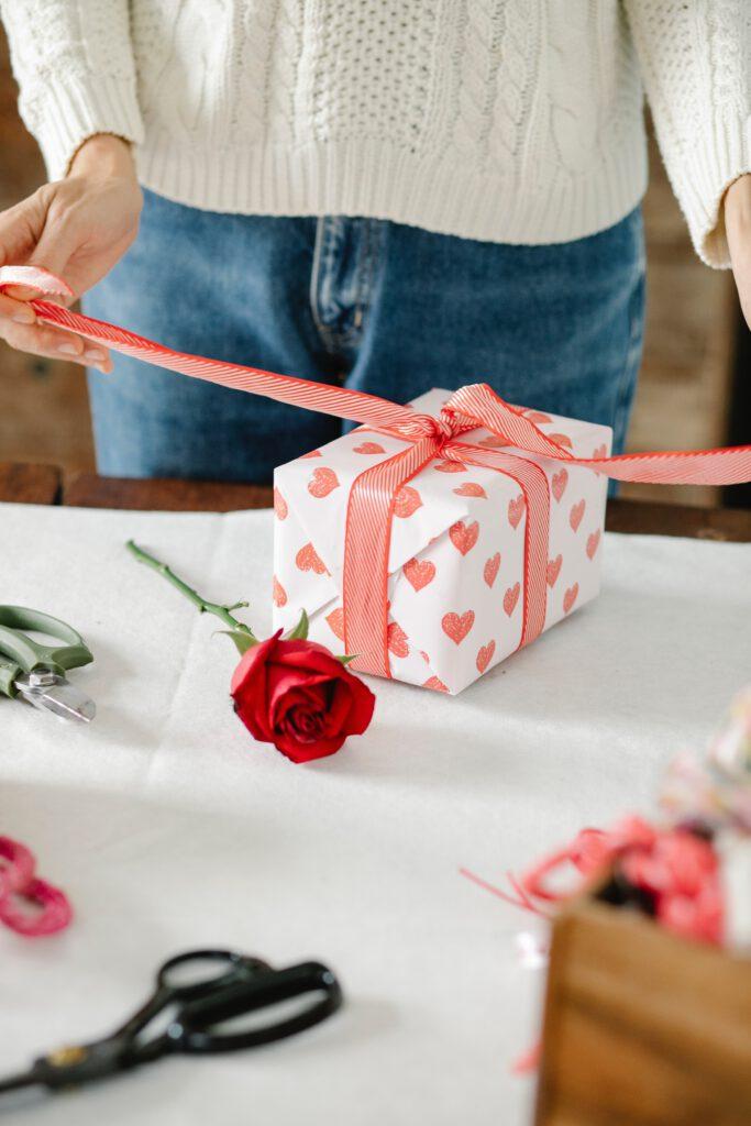 Prezent dla kobiety, kobieta rozpakowuje prezent, stojący na stole. Obok leży róża.