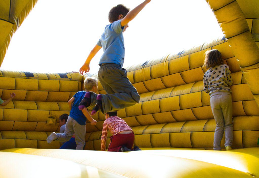 Dzieci skaczą na trampolinie w dmuchanym zamku koloru żółtego. Prezenty na Dzień Dziecka to okazja na wspólną zabawę.