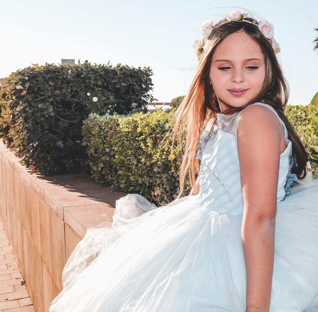 Dziewczynka w białej sukience siedzi na murku. Na głowie ma wianek z róż, w tle niski żywopłot. Prezent na komunię dla dziewczynki