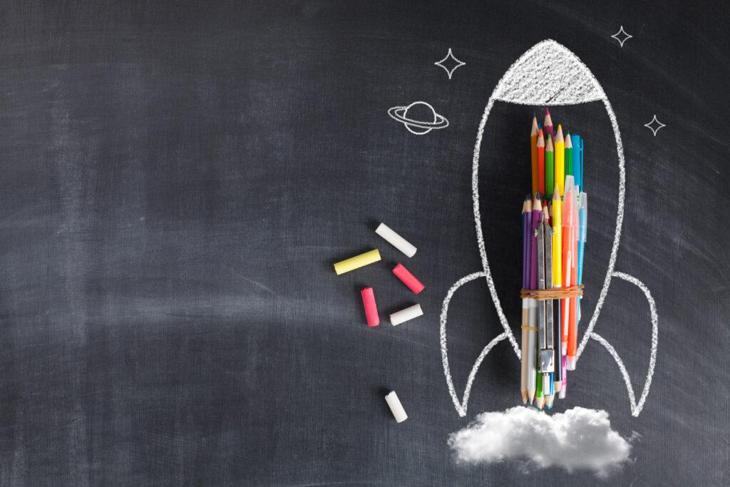 Na szkolnej tablicy namalowana jest rakieta, do której przypięte są kredki i przybory szkolne.