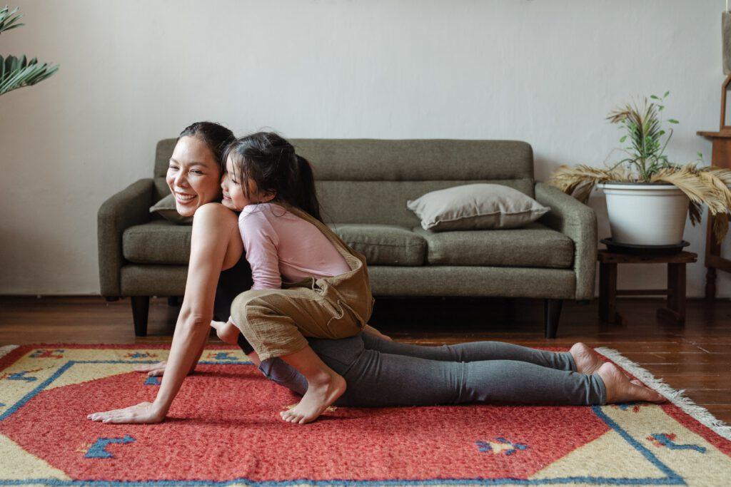 Kobieta, z dzieckiem na plecach, ćwiczy w domu. W tle kanapa, kwiatek i biała ściana. Jeden z 5 sposobów na dbanie o zdrowie w domu.