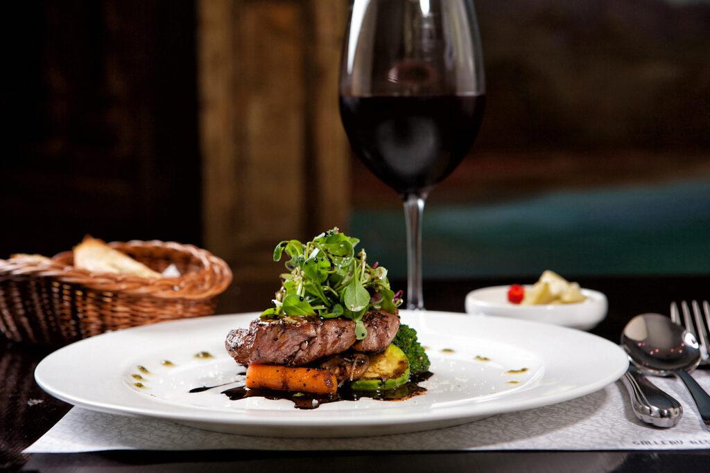 Foodpairing - talerz z wykwintynym jedzeniem, z tyłu kieliszek czerwonego wina, obok sztućce, w tle koszyk z pieczywem.