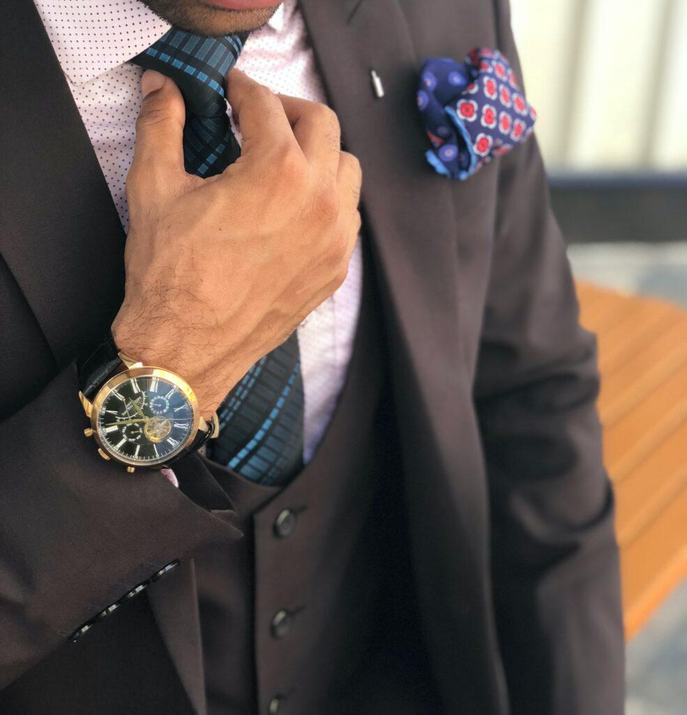 Prezent dla gentlemana: Mężczyzna w garniturze poprawia krawat. Na ręku zegarek, nie widać twarzy.