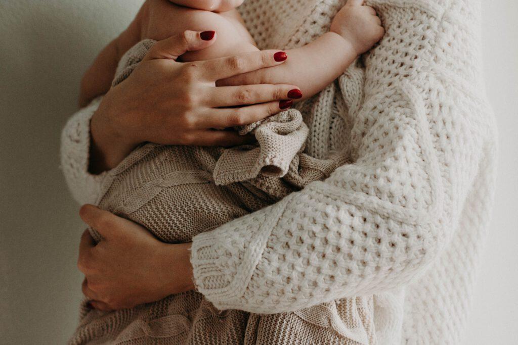 Prezent dla młodej mamy: kobieta trzyma dziecko na rękach. Nie widać twarzy.