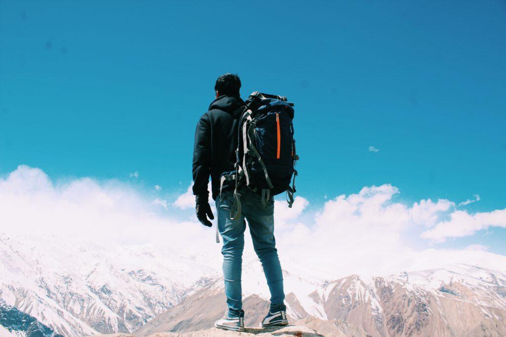Prezent dla podróżnika: mężczyzna z plecakiem stoi na szczycie góry i patrzy na inne szczyty gór
