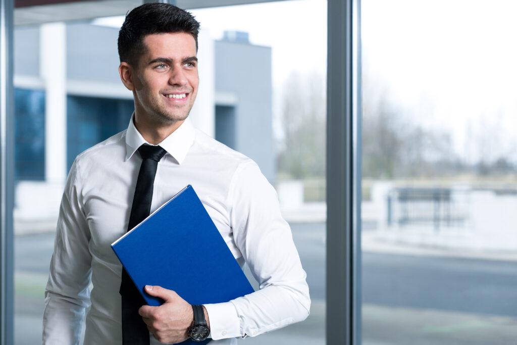 Prezent dla promotora: na zdjęciu uśmiechnięty, elegancko ubrany mężczyzna, trzymający niebieską teczkę z dokumentami.