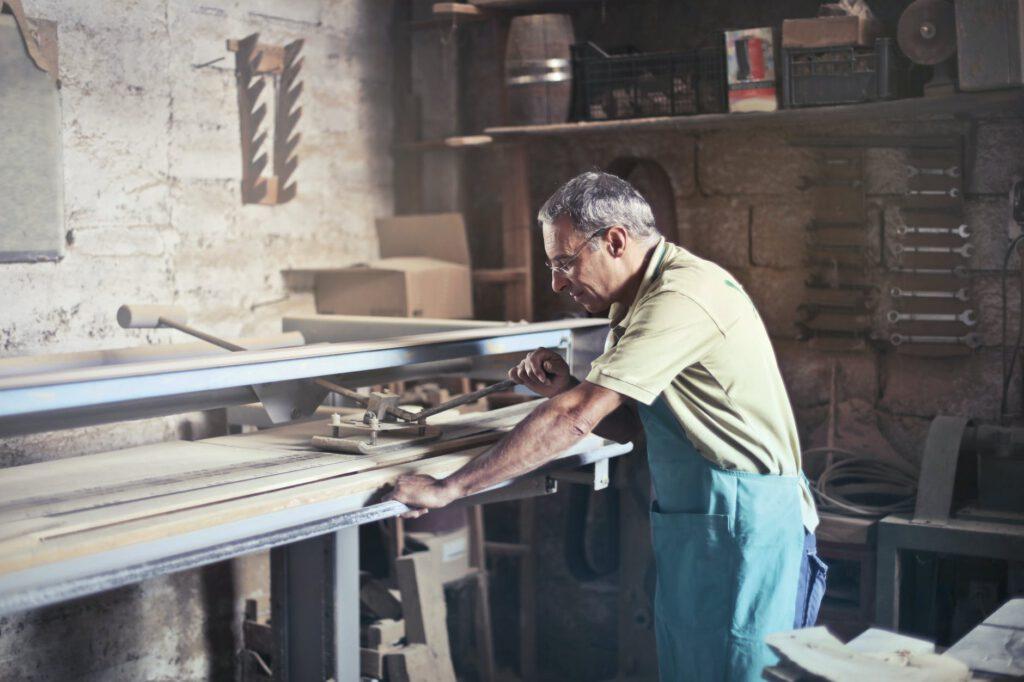 Kurs stolarski - mężczyzna szlifuje drewno w warsztacie stolarskim.