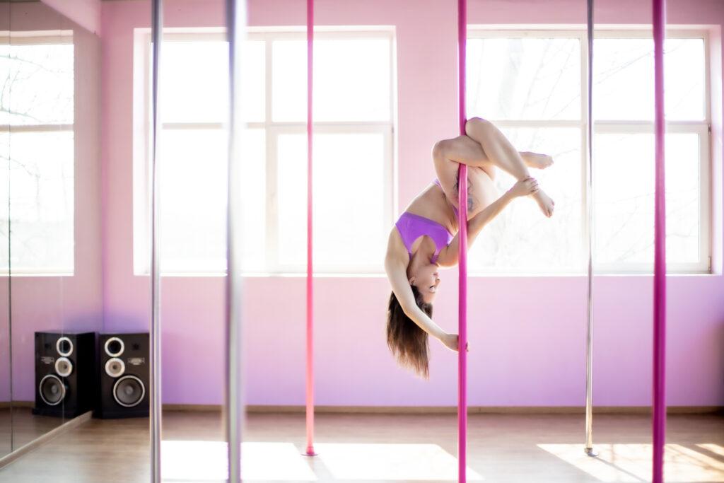 Pole Dance - kobieta zawieszona na rurce w akrobacji