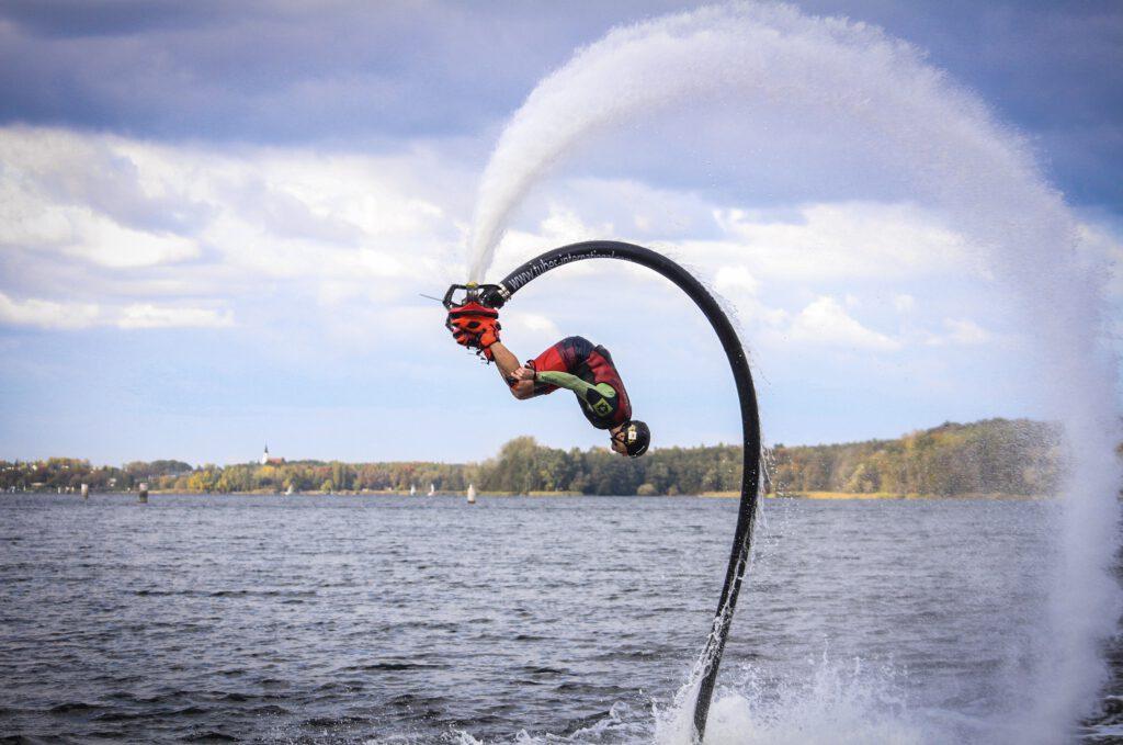 Flyboard - mężczyzna unosi się w powietrzu na latającej desce i wykonuje akrobacje