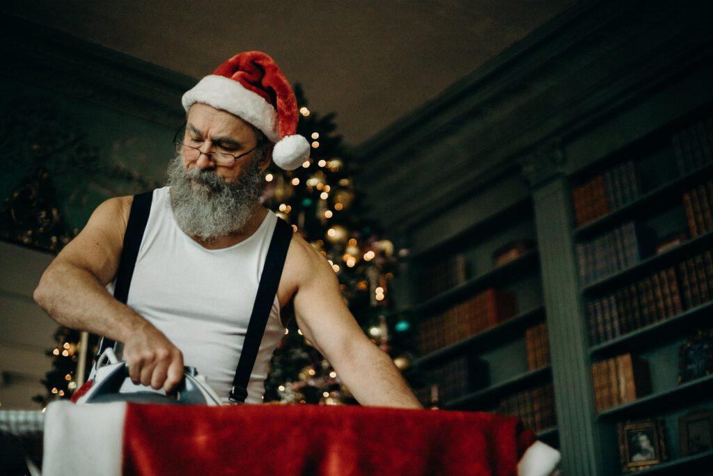 Święty Mikołaj - mężczyzna w białym podkoszulku i czerwonej czapce prasuje czerwony kubrak