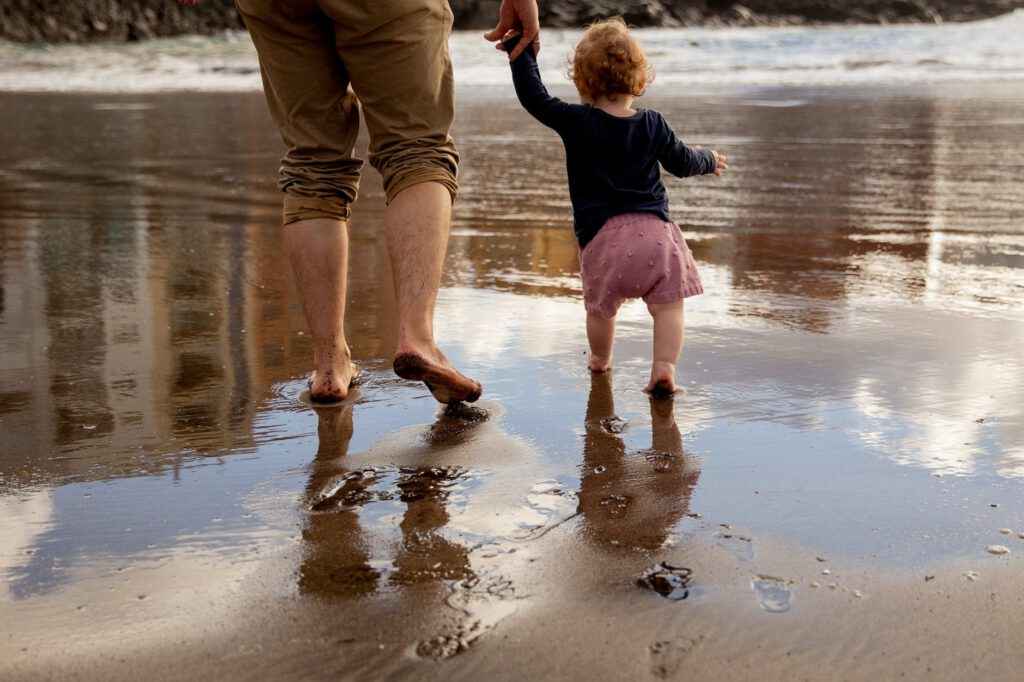 Prezent dla młodego taty - mężczyzna trzyma za rękę małe dziecko