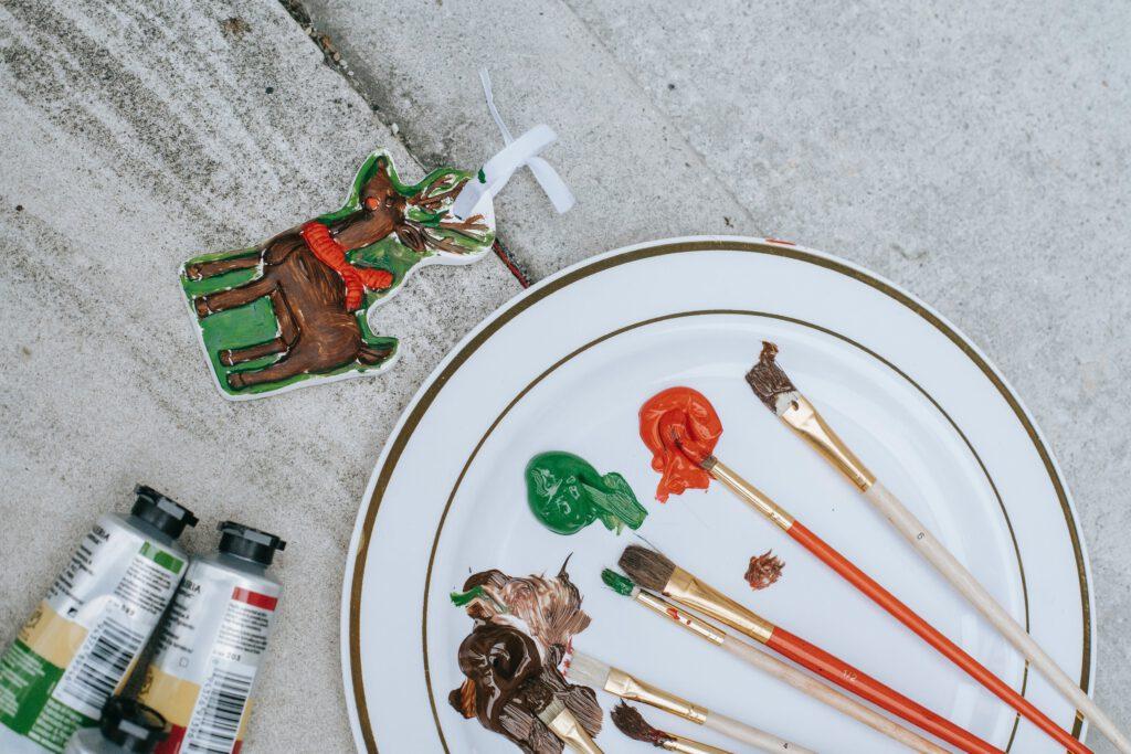 Prezenty na Święta DIY - na talerzu leżą pędzle umazane farbą, obok ozdoba świąteczna