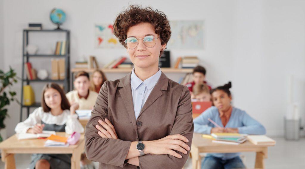 Prezent na Dzień Nauczyciela - nauczycielka stoi na przodzie, za nią siedzą dzieci w ławkach.