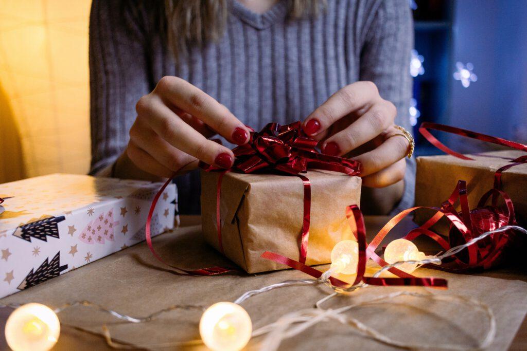 Co kupić tacie na święta - kobieta pakuje prezent z kokardą