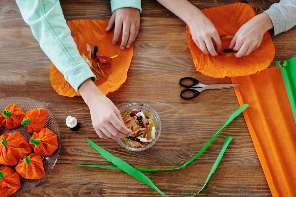 Zabawy na Halloween -diwe osoby robią halloweenowe dekoracje z żelków i pomarańczowej bibuły