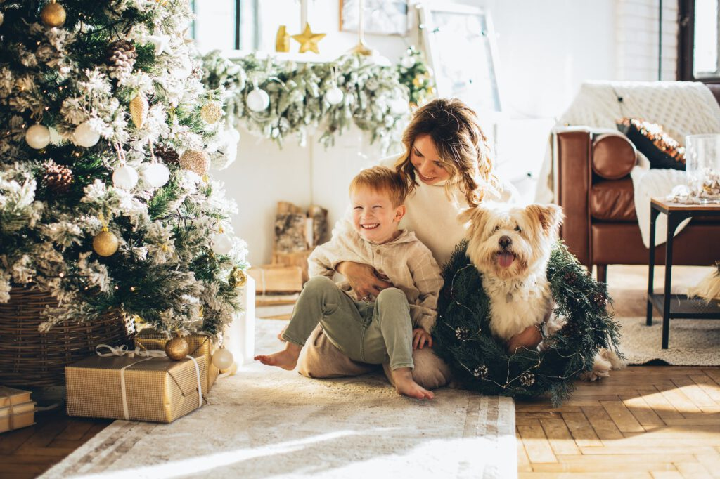 Prezent na Święta dla rodziny - kobieta siedzi razem z dzieckiem i psem obok przystrojonej choinki